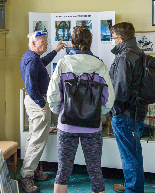 Photo of docent in front of a display explaining the workings of the lighthouse's light