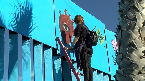 Chula Vista illustrator, Michelle Ruby Guerrero paints at the border fence.