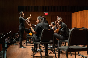 Teacher-of-record Latifat Momson conducts Chicago Baker Prep students at a 2019 showcase concert at University of Chicago's Logan Center.