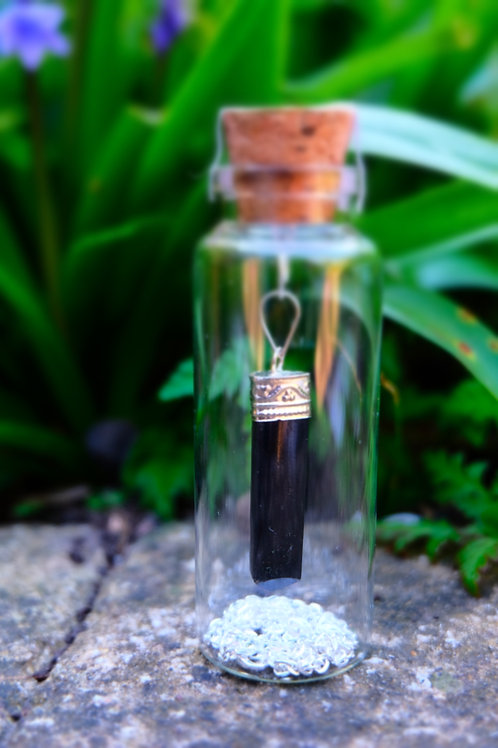 Tourmaline pendent with silver coloured chain in bottle.