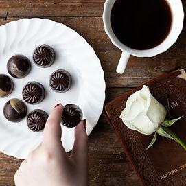 hand picking up chocolates , coffee flat