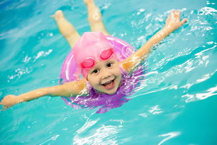 Funny little girl swims in a pool in an