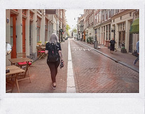 A candid polaroid of Abbi in Amsterdam carrying a polaroid camera.