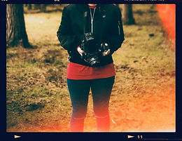 A picture of Abbi holding a medium format camera in the forest.