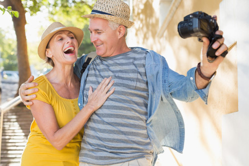 happy-tourist-couple-taking-a-selfie-in-