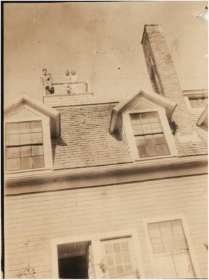 """In this picture taken of the """"crows nest"""" the caretaker GodbergGulbrandsen is sitting on the railing and Evelyn Briggs and Louise Thomas stood next to him."""