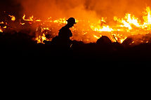 Silhouette of a smoke jumper fireman walking the parameter of a wildfire.jpg