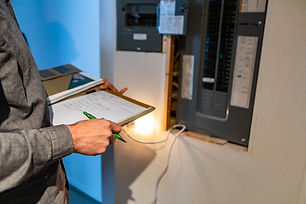 home Inspector in front of electric distribution board during inspection, selective focus