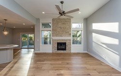 Stone Fireplace, White Mantle, White Grout, Large Windows On Each Side