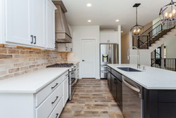 Kitchen with Brick Backsplash, Wood Hood, Open Floor Plan