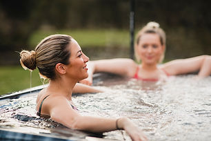 Mid adult woman relaxing in a hot tub with her friends..jpg