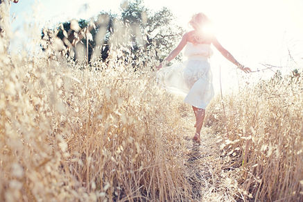Image of lady walking thru a path in a wheat field.