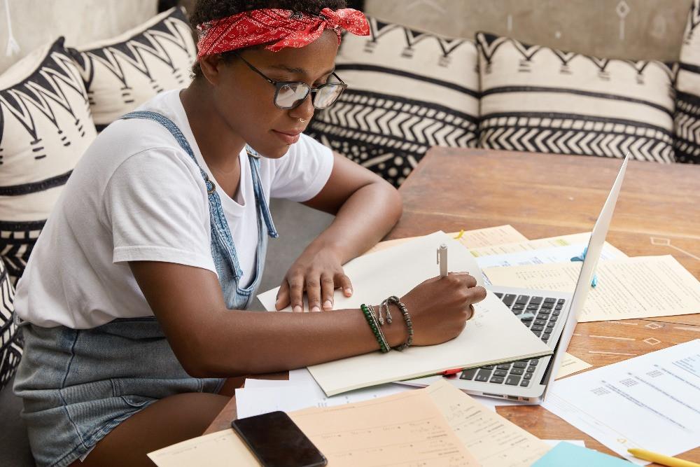 mulher negra escrevendo e notebook