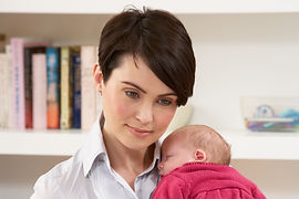 Woman With Newborn Baby Working From Hom