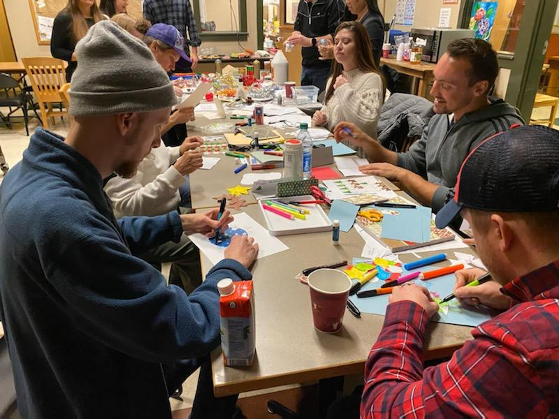 Volunteers and residents create holiday cards at Plymouth Housing (Photo Credit: YP Impact)