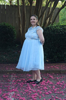 photo of Alison Rushing wearing a blue dress standing on red flower petals.