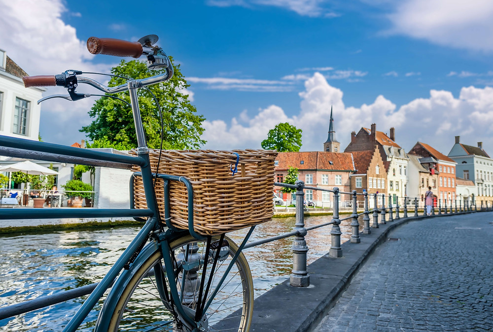Bicycle leaning against railing on a path that runs along the river.
