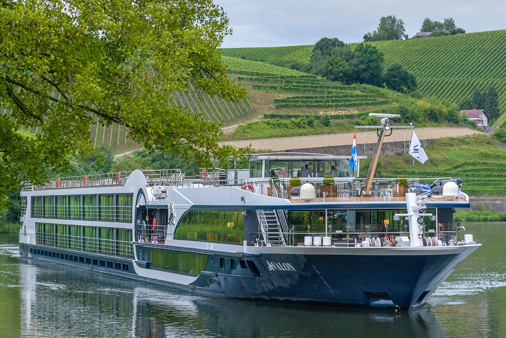 River cruise boat floats along countryside.