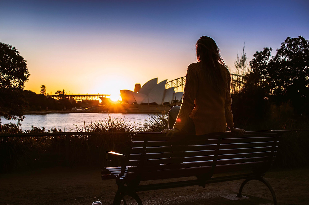 Woman watching sunset over Syndey Opera House