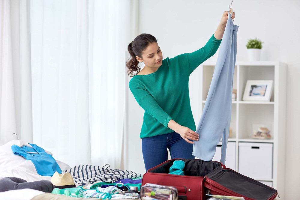 Woman holds blue capris above open suitcase sitting on bed next to other clothing.