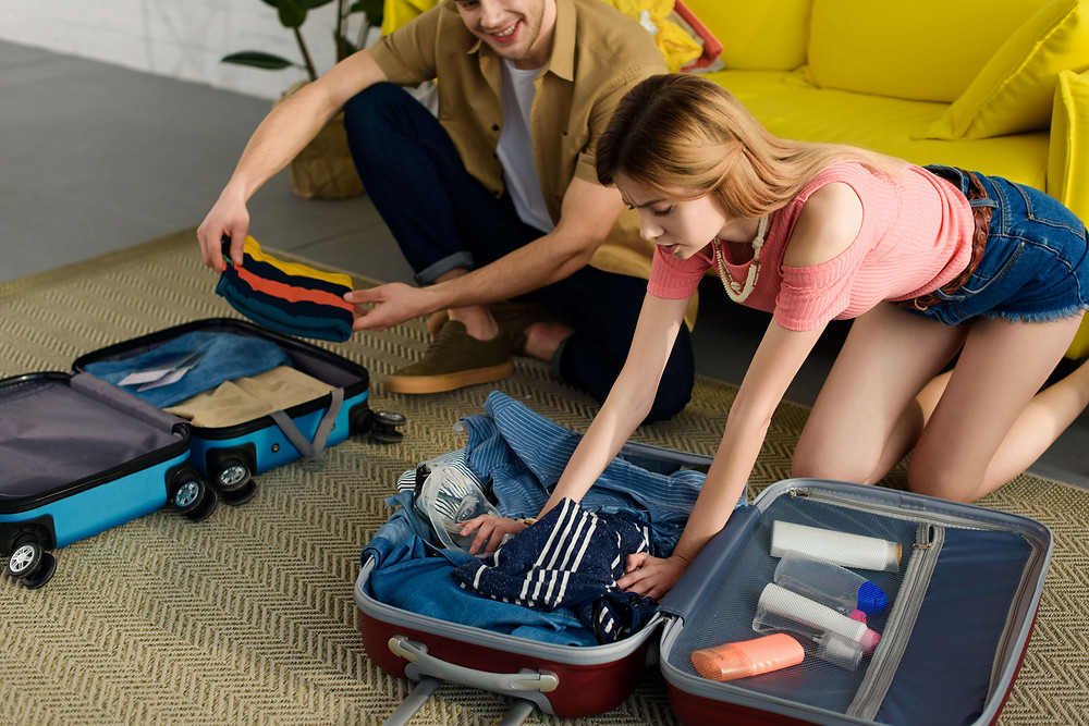 Couple struggling to fit clothing into luggage.