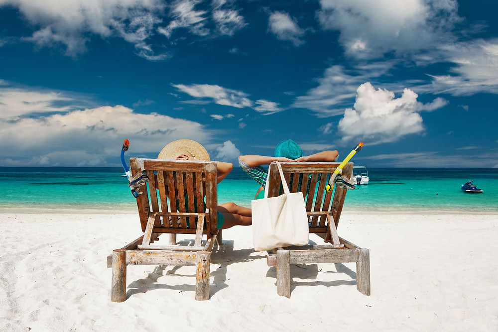 Couple sunbathing in lounge chairs on the beach in the Maldives