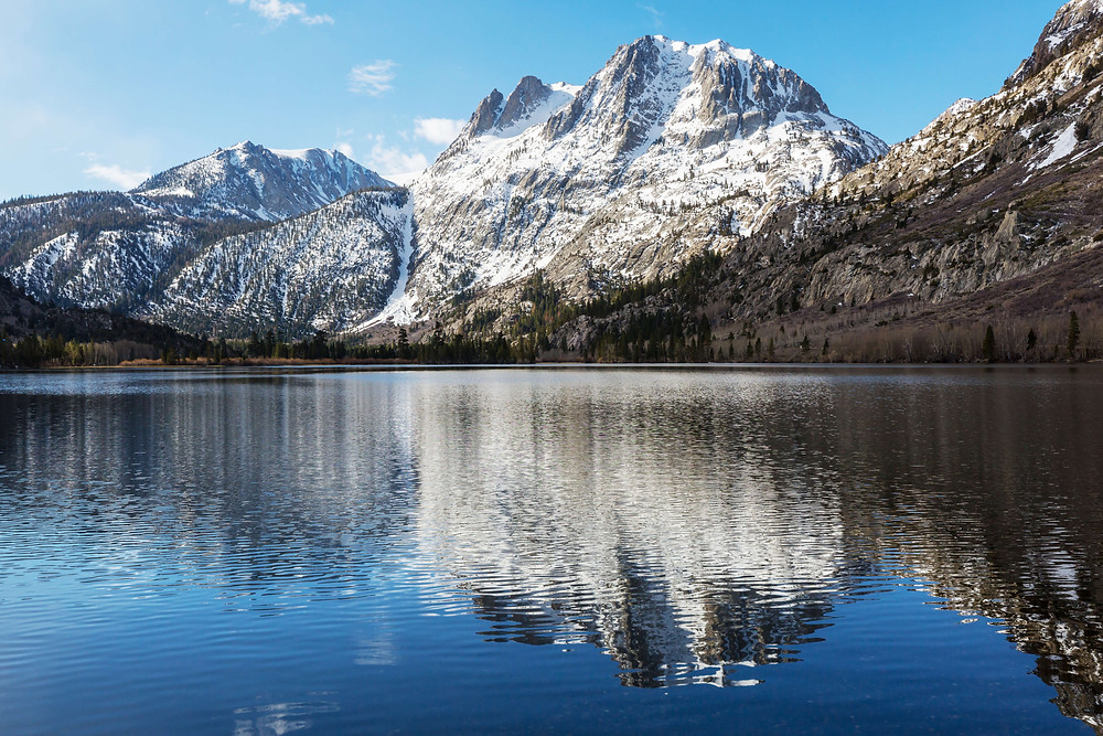 Snow-covered mountain range reflects in a lake in the Sierra Nevada