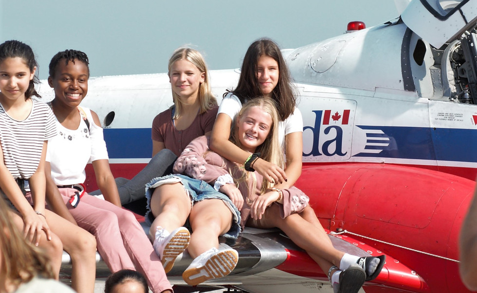 Students sit on the wing of the plane fo