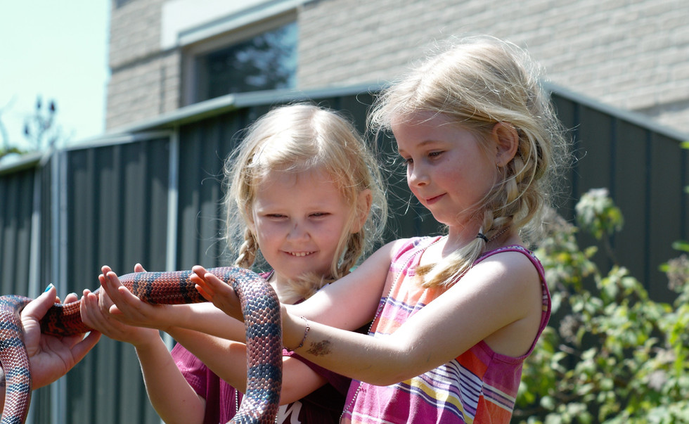 Alice and Mille McGeachin, hold a snake