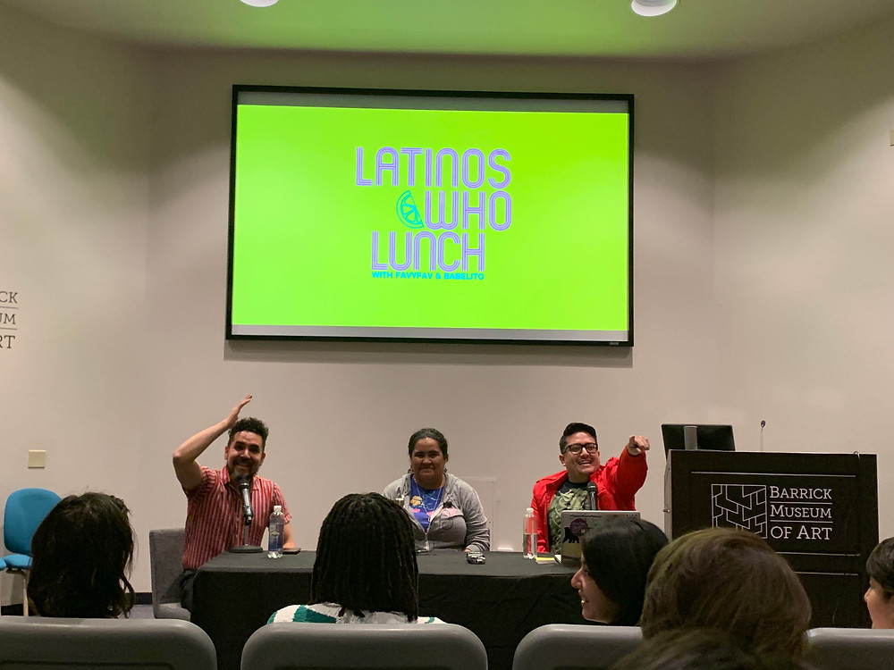 Emmanuel Ortega, Erika Abad, and Justin Favela sit at a table facing a crowd of listeners while smiling and gesturing to the audience. The Latinos Who Lunch logo is projected on the screen behind them in vivid lime green.