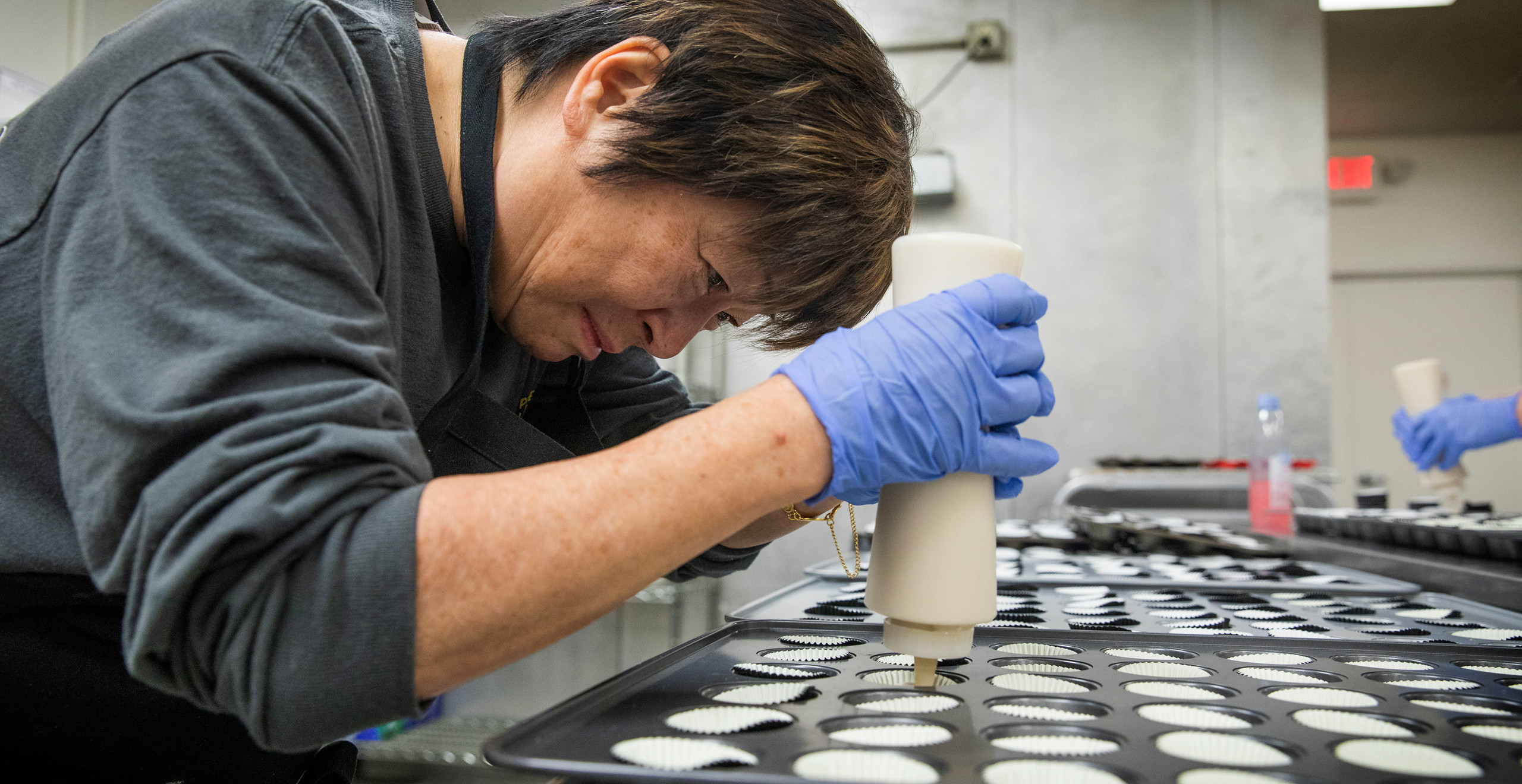 A middle-aged Asian volunteer leans over a mini cupcake pan with intense focus, smiling slightly as she fills the pan.