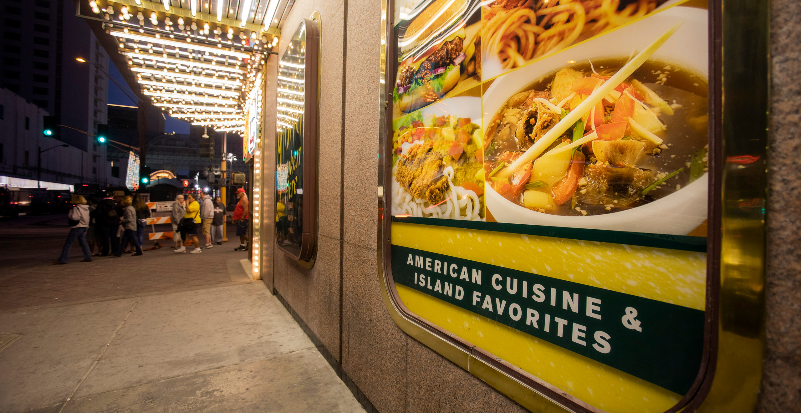 "A close, angled shot of signboards outside the Cal, advertising ""American Cuisine & Island Favorites."" It features pictures of a burger, noodles, katsu, and oxtail soup."