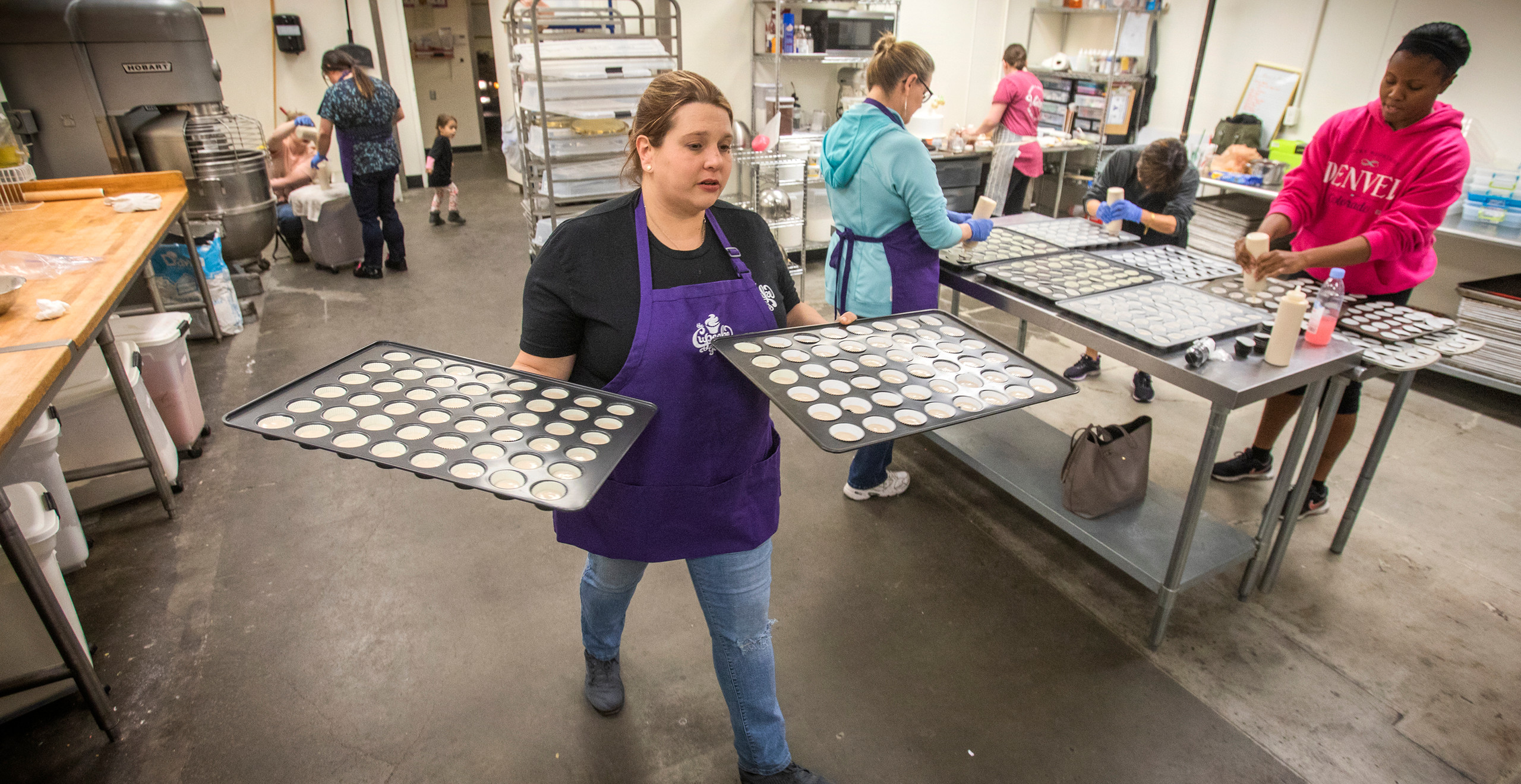 A volunteer wearing a purple apron with the Cupcake Girls' logo on it carries two mini cupcake pans through an industrial kitchen, while 5 other volunteers (and one cute toddler) are busy in the background.