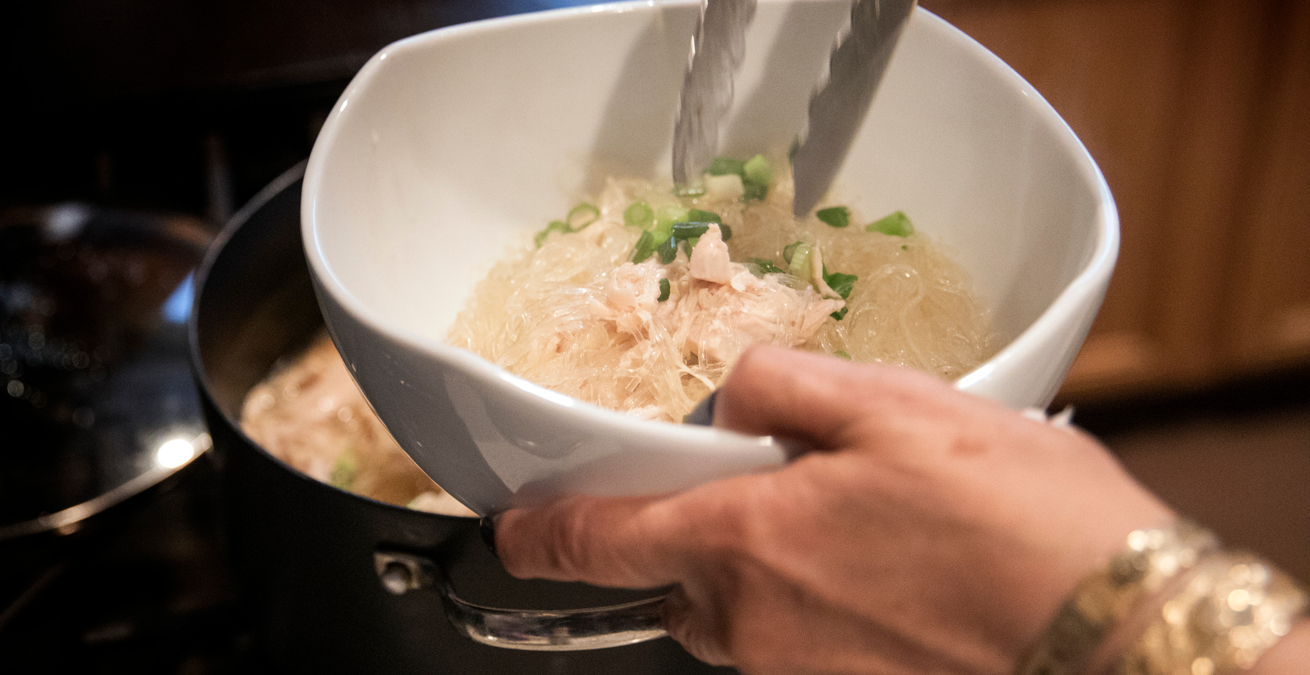 A closeup of Haunani's hands as she transfers the cooked rice noodles, chicken and green onions into a white serving bowl using silver tongs.