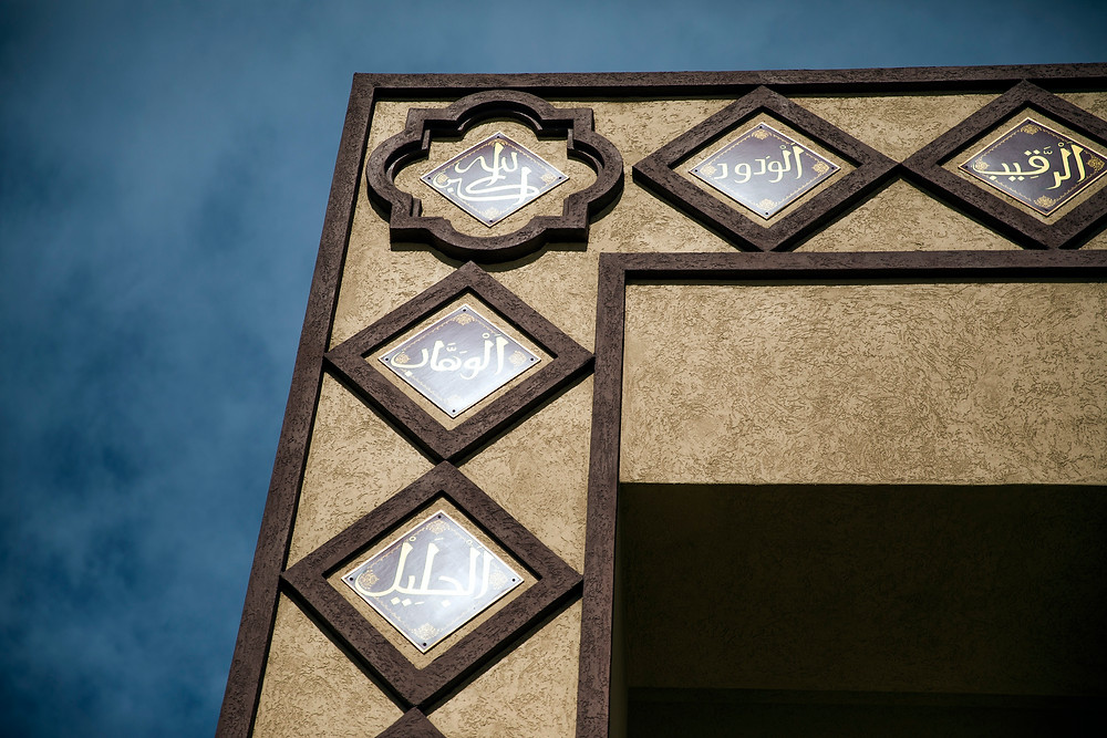 Some of the 99 names of God inscribed in Arabic around the entrance at the Masjid Ibrahim, set against a deep blue sky. Photo by Jeff Scheid.