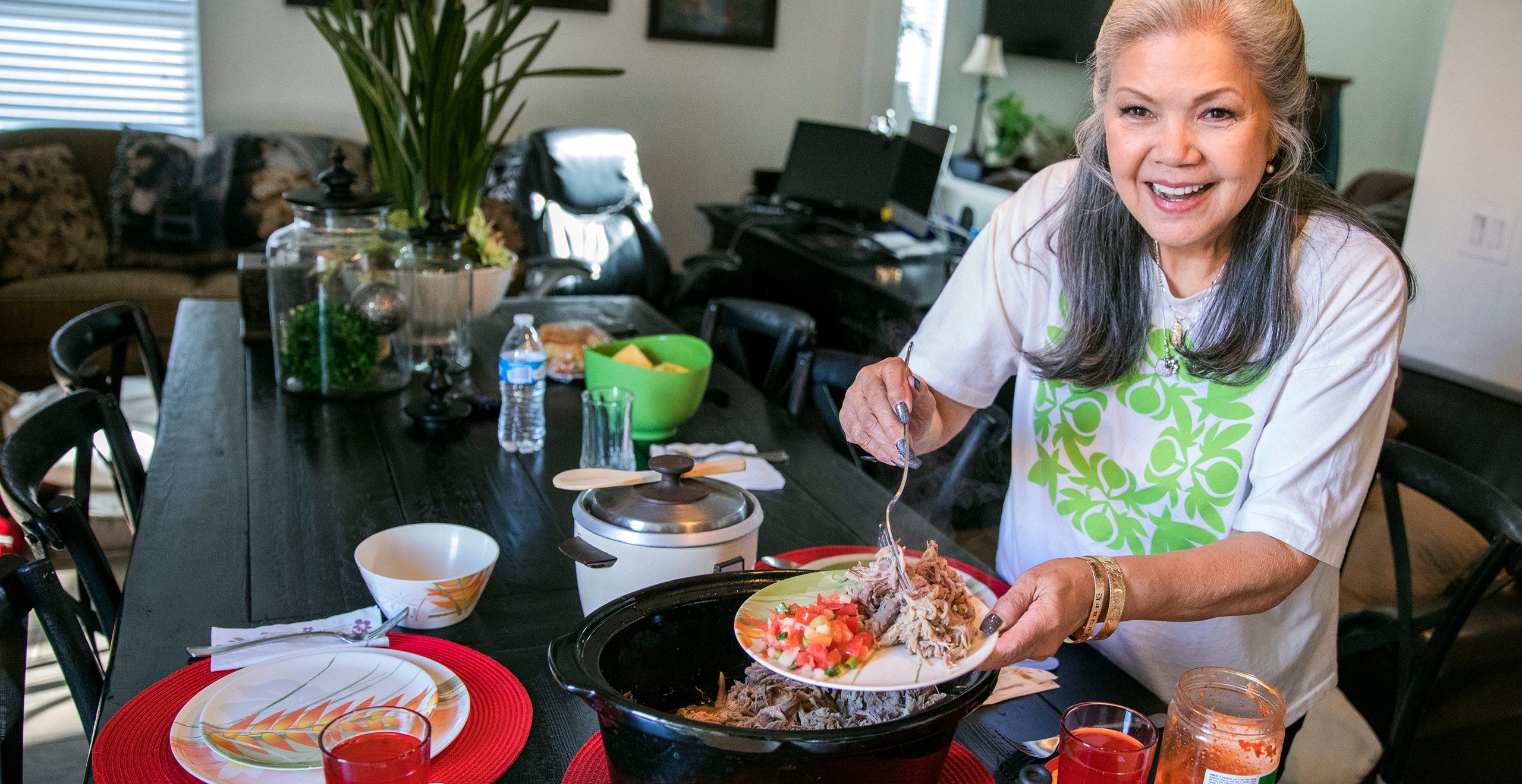 Haunani looks up, smiling, while dishing up some kalua pork on a dinner plate at the dining room table. She is a beautiful middle-aged woman with long gray hair half pinned up, round cheeks, and eyes that smile.