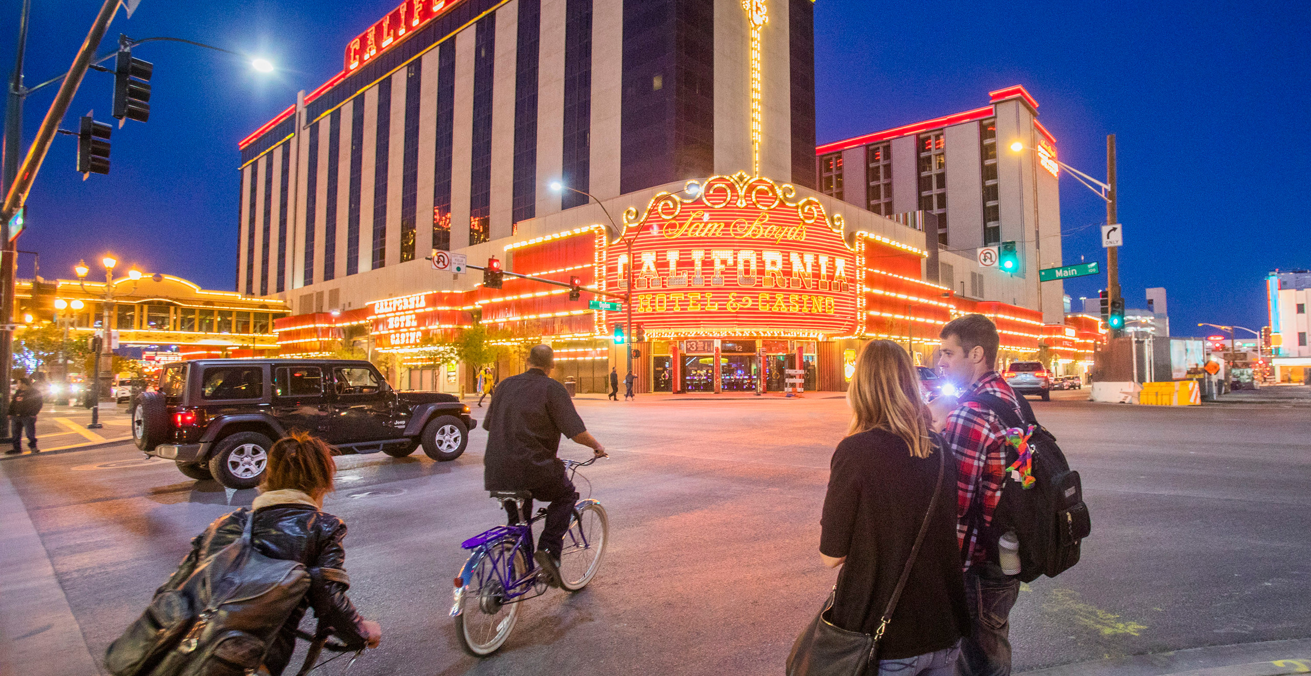 An exterior shot of the California Hotel and Casino, featuring its brightly lit signage, in the early evening against an indigo sky. Pedestrians and cyclists cross the street in the foreground.