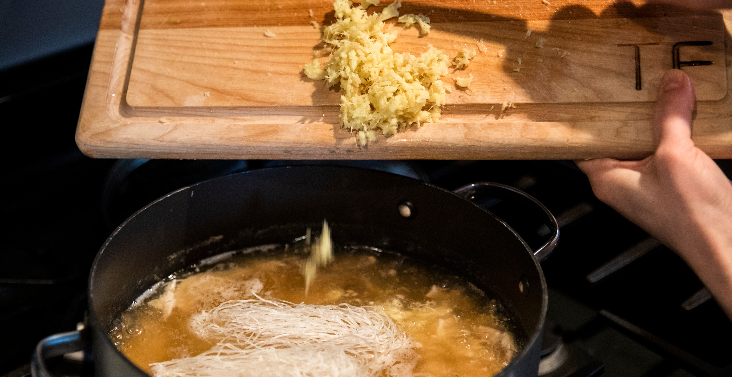 A hand scrapes chopped ginger from a wooden cutting board into a boiling pot of chicken broth and rice noodles.