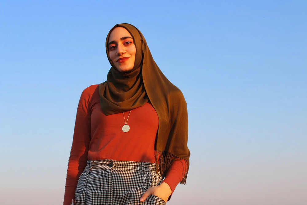 Profile image of Summer Thomad, wearing a deep maroon hijab and red shirt, against a desert sunset.