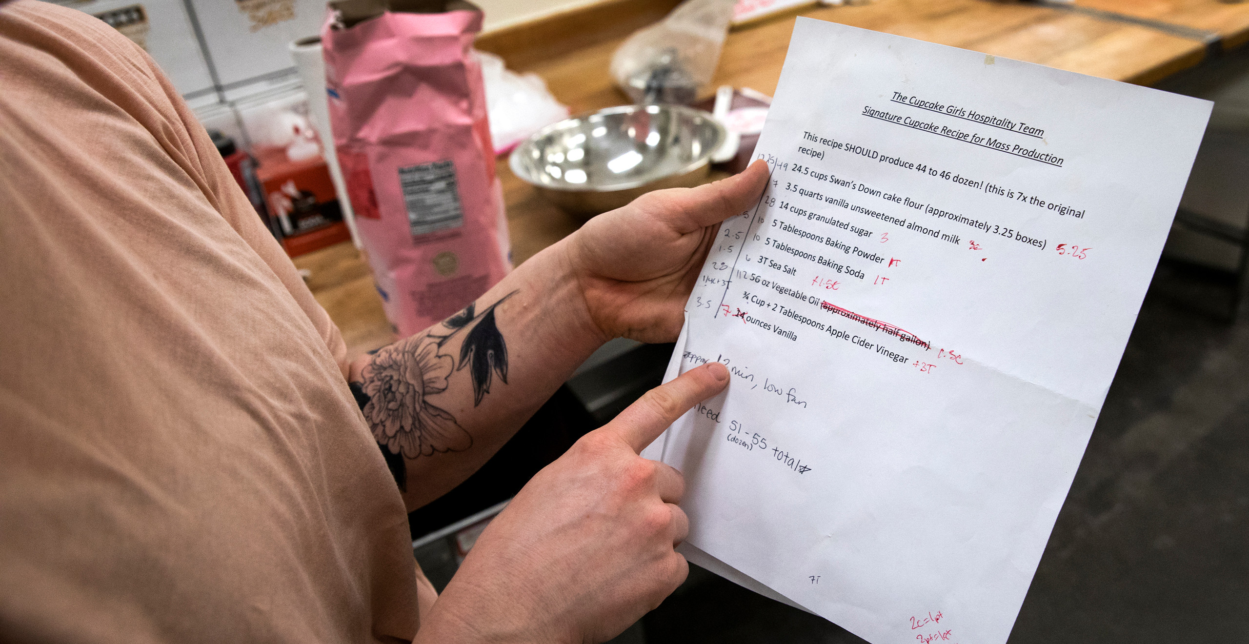 """A closeup of someone's hands holding a recipe that reads """"The Cupcake Girls Hospitality Team Signature Cupcake Recipe for Mass Production."""" In the background you can see a pink bag of sugar and a silver mixing bowl."""