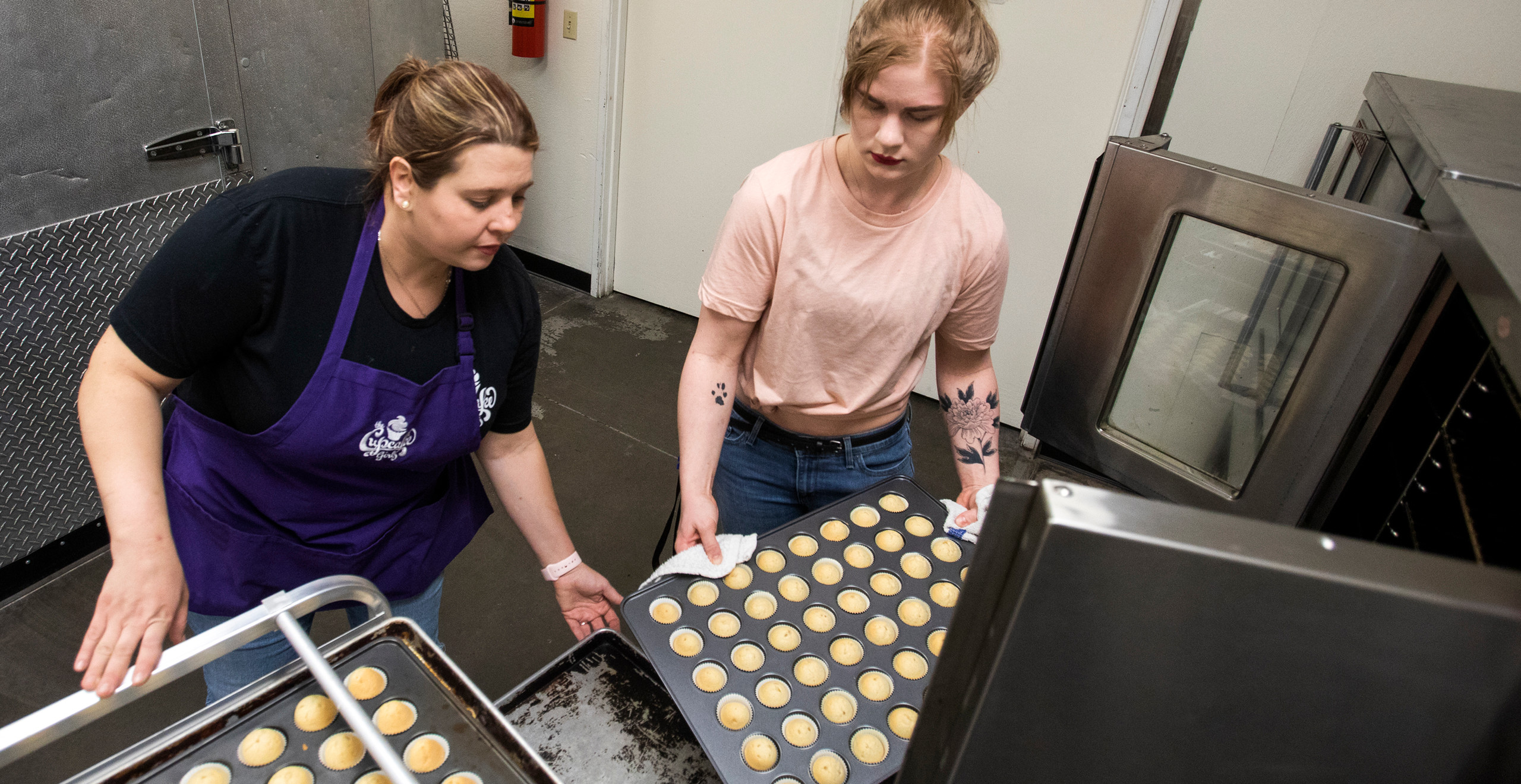 The purple-aproned volunteer and another volunteer in a pink tshirt pull out two trays of freshly-baked, golden-hued mini cupcakes.