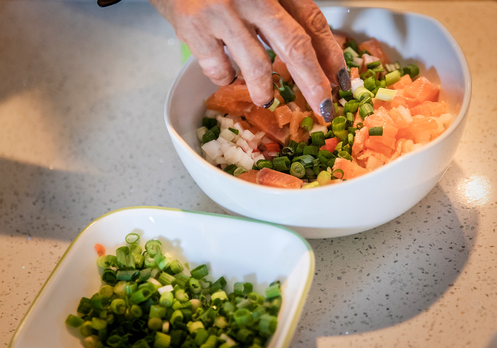 A woman's hand reaches in to mix a bowl of cubed salmon mixed with diced onion, tomato and green onion. This is lomi salmon.
