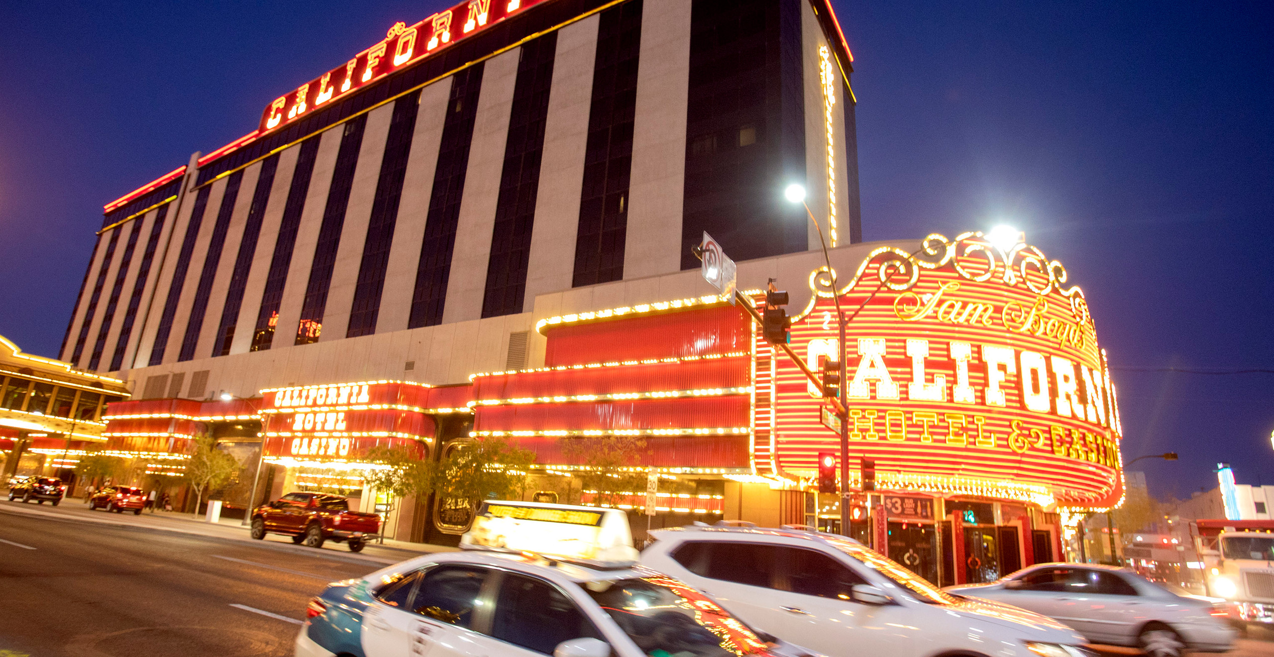 A closer view of the California Hotel and Casino's exterior, with the bright orange and yellow lights contrasting against an indigo sky.