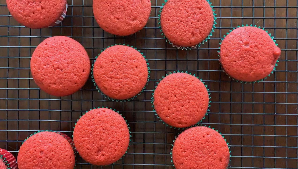 An overhead shot of 10 or so bright red cupcakes cooking on a wire rack