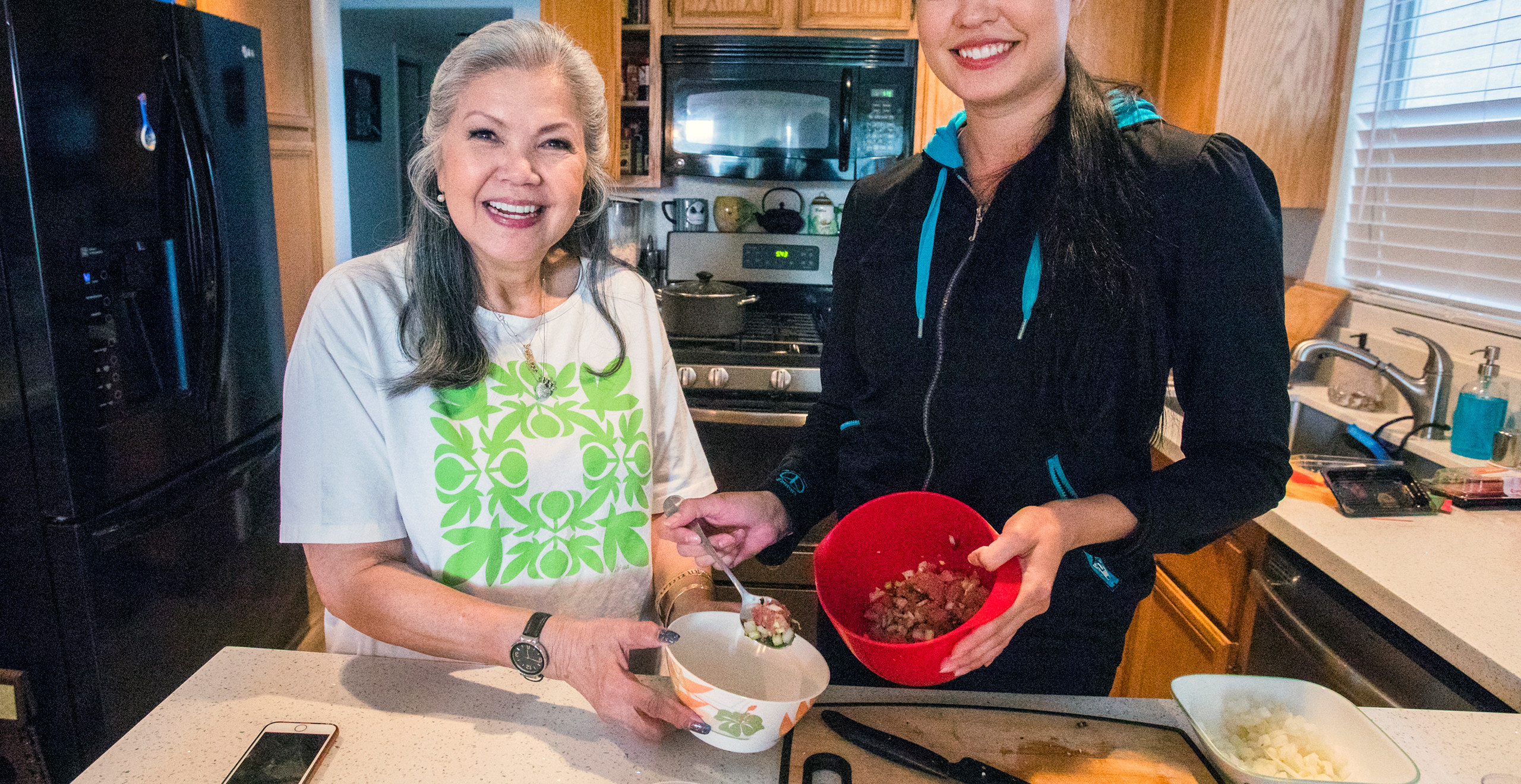 Haunani, who is wearing a Hawaiian quilt-patterned tshirt, stands with her daughter Taylor at the counter while they make inamona poke, a raw tuna dish.