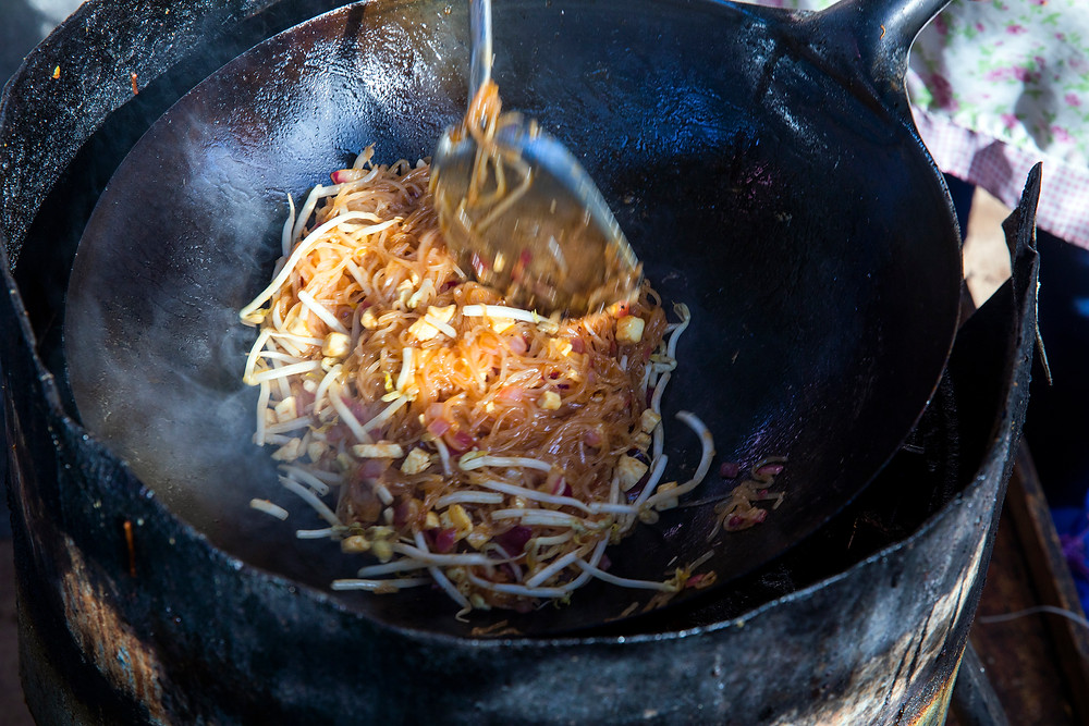 An overhead close up shot of pad thai being cooked in a dark black wok while a blurry spatula stirs the mung bean and noodle mixture.
