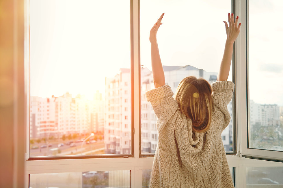 Woman near window raising hands facing t