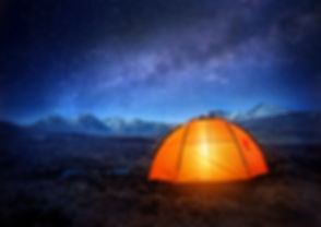 A tent glows under a night sky full of s