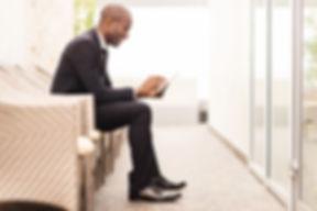 Trygge forretningsmand venter på et inte