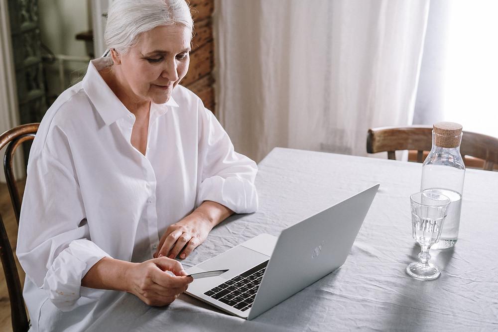 Uma mulher sentada olha para um notebook. Ela veste uma camisa branca e tem os cabelos brancos. Na mesa, além do computador, temos também uma garrafa com água e um copo. A luz da cena é diurna.